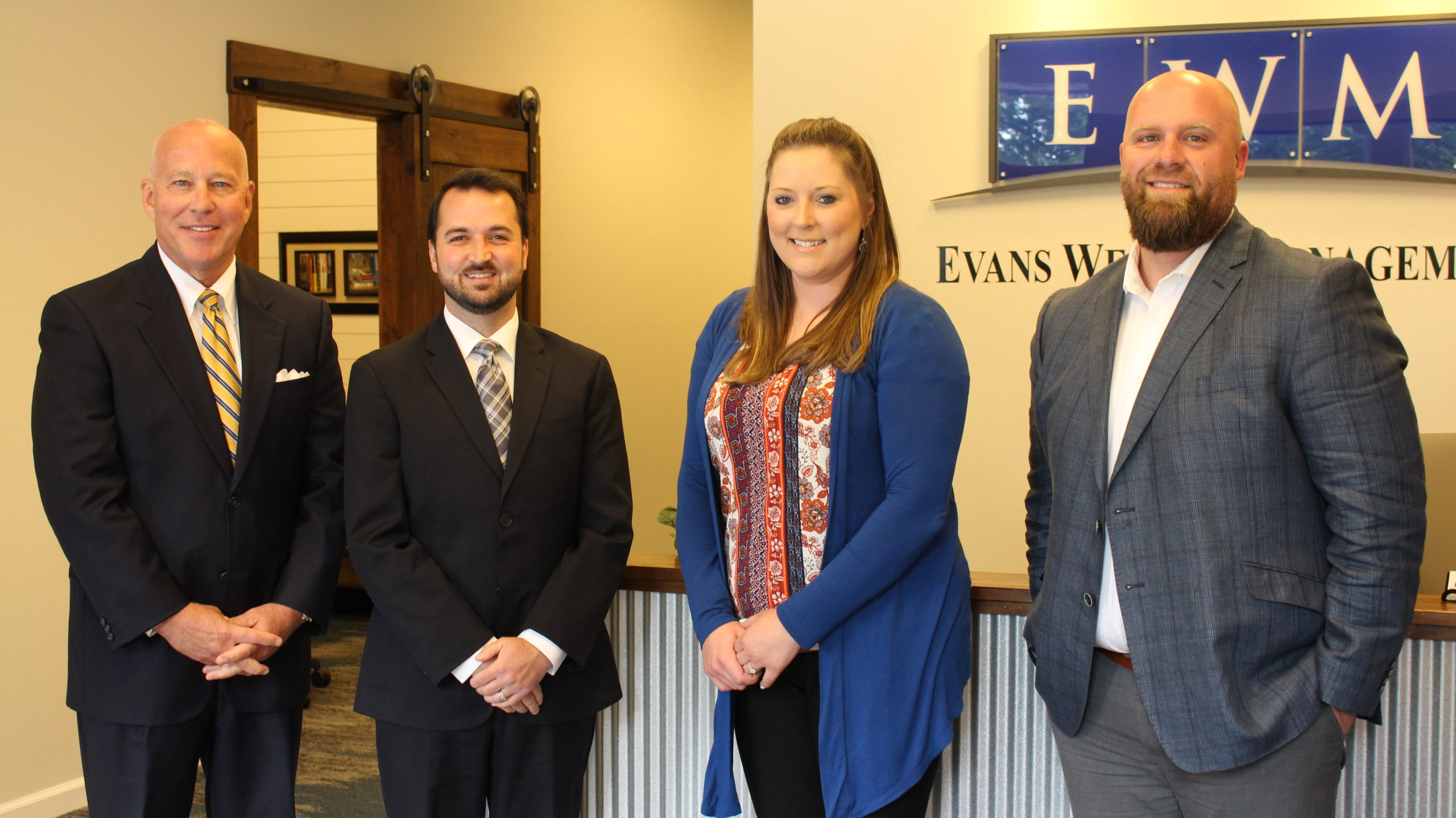 Evans Wealth Management Team Photo Standing in loby